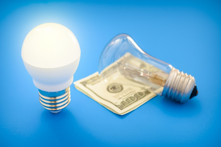 Led light bulb lay next to incandescent bulb and dollar bill. Concept energy saving